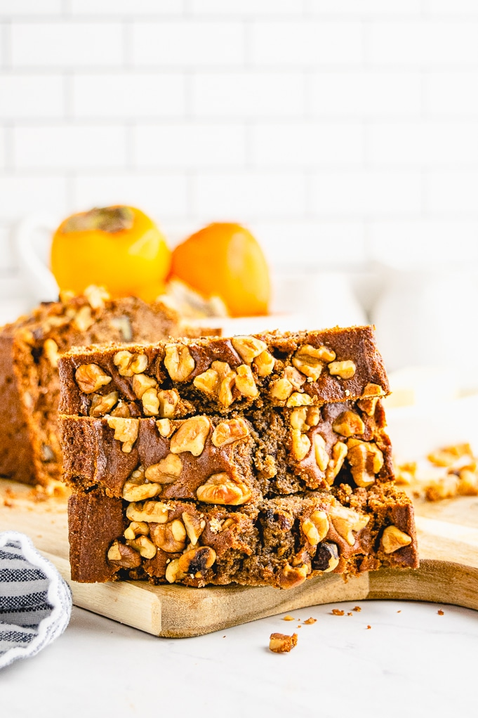 Sliced quick bread topped with walnuts.