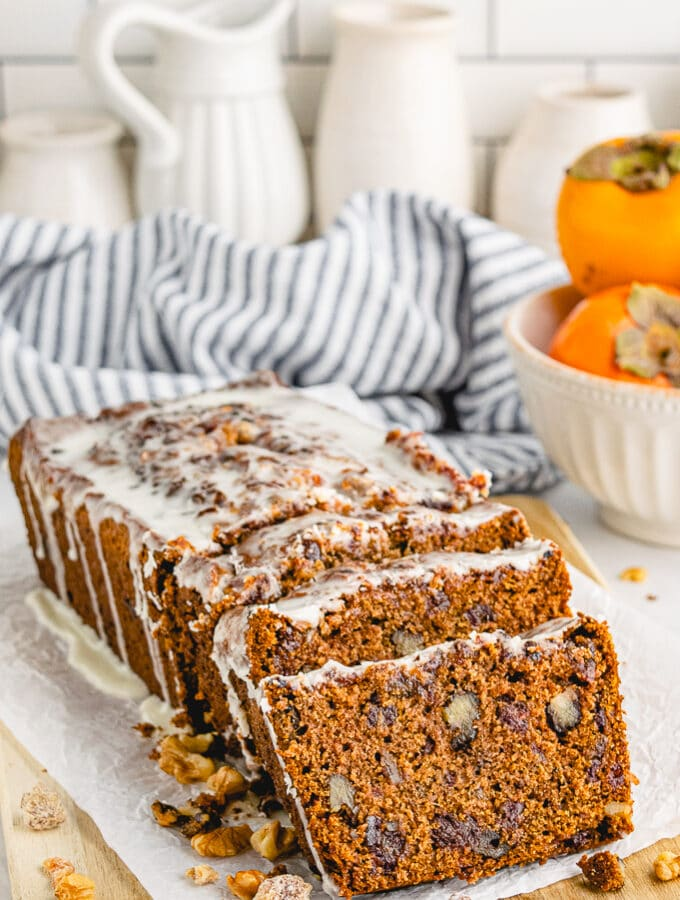 Sliced persimmon bread with nuts and topped with a glaze on a cutting board.