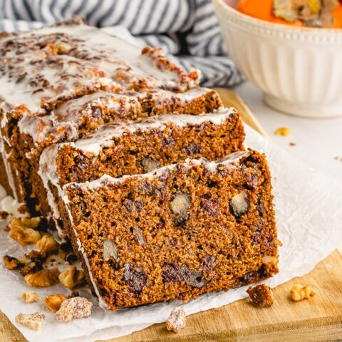 A loaf of persimmon bread sliced on a cutting board.