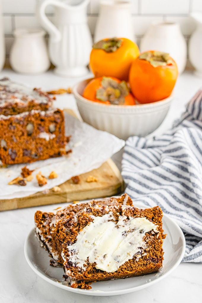 Sliced persimmon bread on a white plate with fresh persimmons in the background.