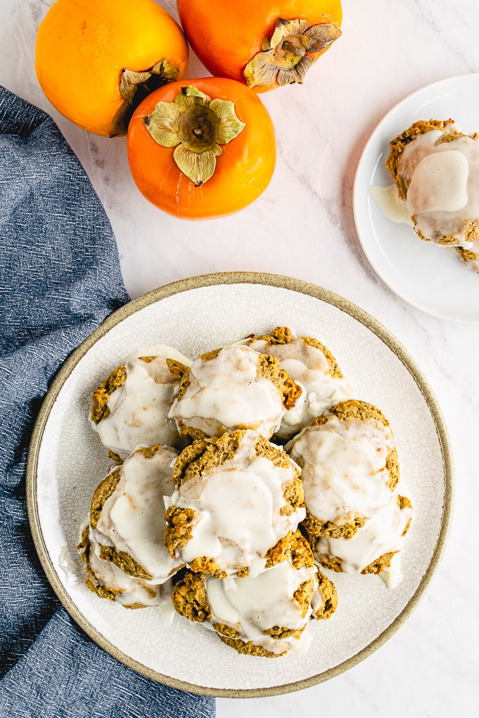Top view of persimmon cookies on a white plate topped with glaze.