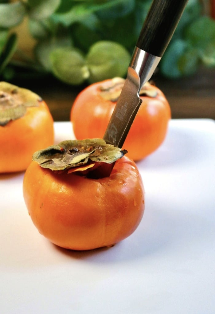 Cut the tops off of a persimmon before slicing