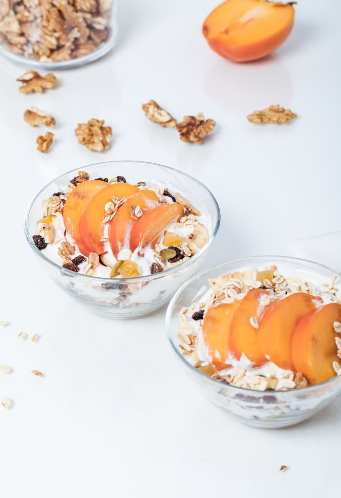 slices of persimmon on top of yogurt with granola in a clear bowl.