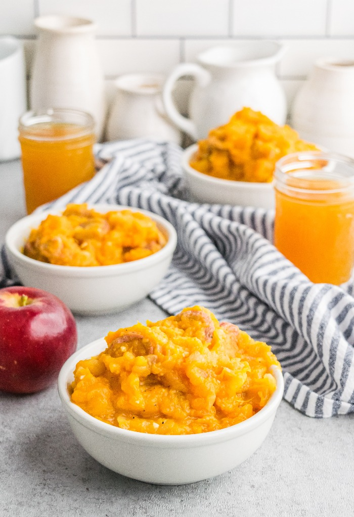 White serving bowls with mashed sweet potatoes, apple and sausage for a filling savory breakfast.