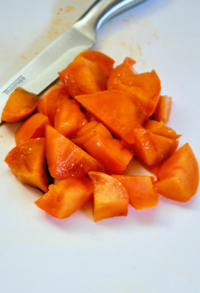 Diced persimmons on a white cutting board.