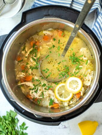 Cooked lemon chicken orzo soup in an Instant Pot with a large spoon ready to scoop into bowls.