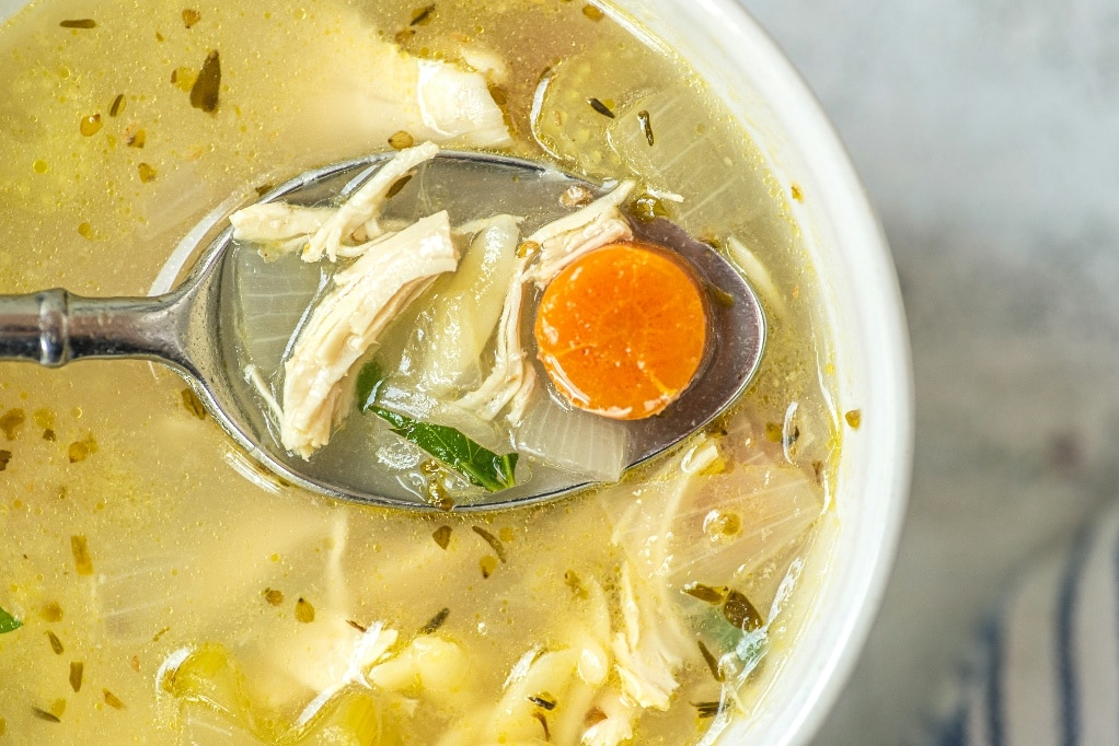 Close spoonful view of lemon chicken orzo soup.