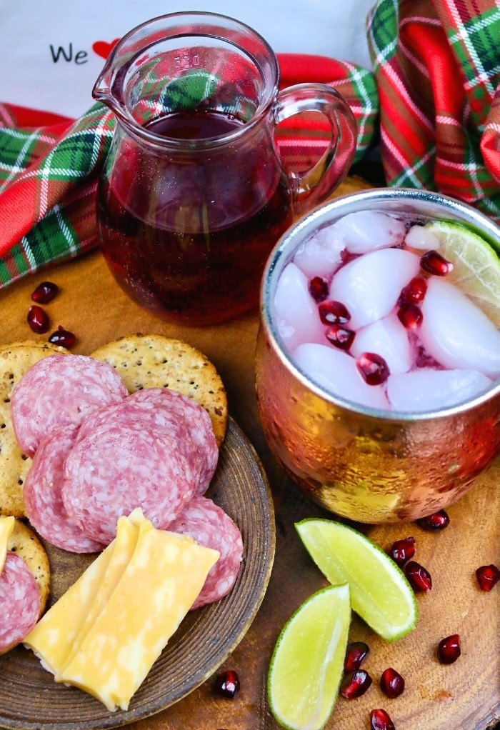 Cocktail in a copper mug with cheese and salami ready to be eaten.
