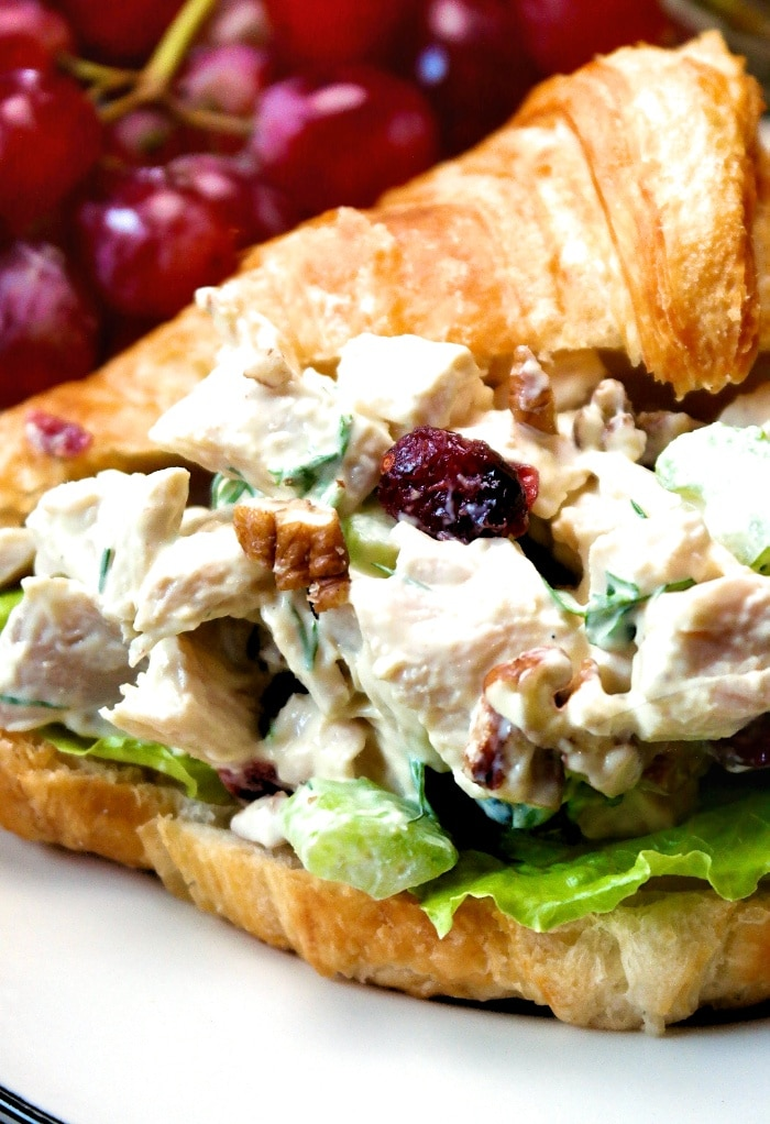 A turkey salad sandwich with croissant bread on a white plate.