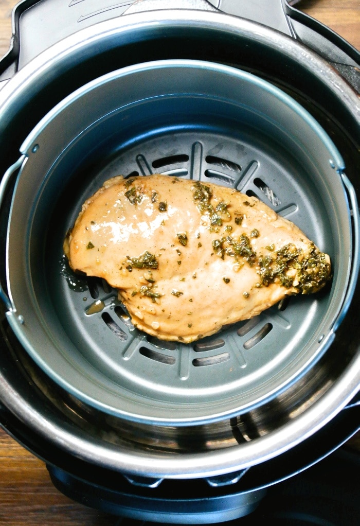 A top view of chicken breast in an air fryer ready to cook.