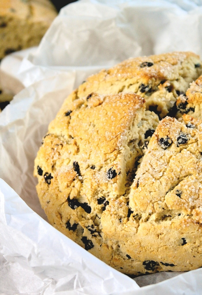 A close up view of Irish soda bread in white parchment paper.