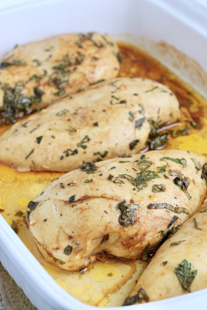 A white baking dish with cooked chicken breasts.