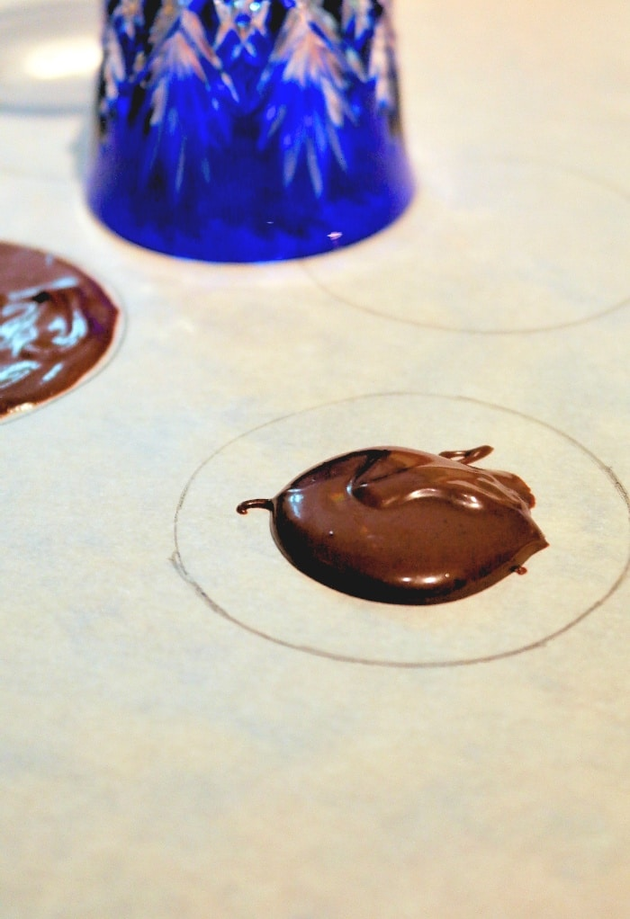 A round circle on parchment paper to make a disk to cover chocolate mold.