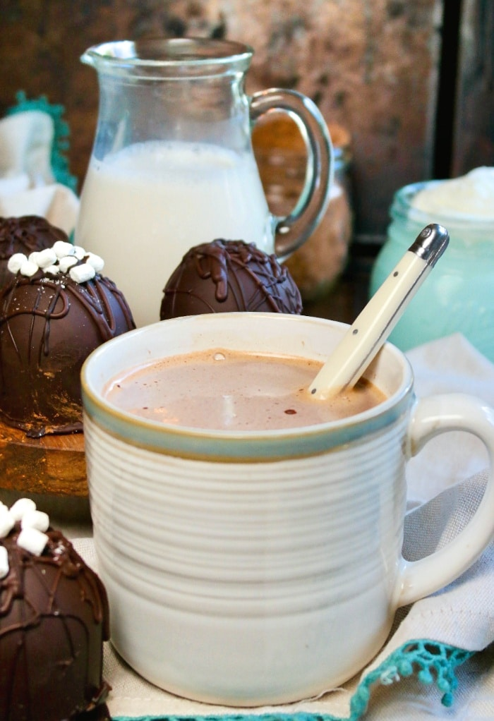 Hot chocolate in a cream mug with a spoon in the middle to stir.
