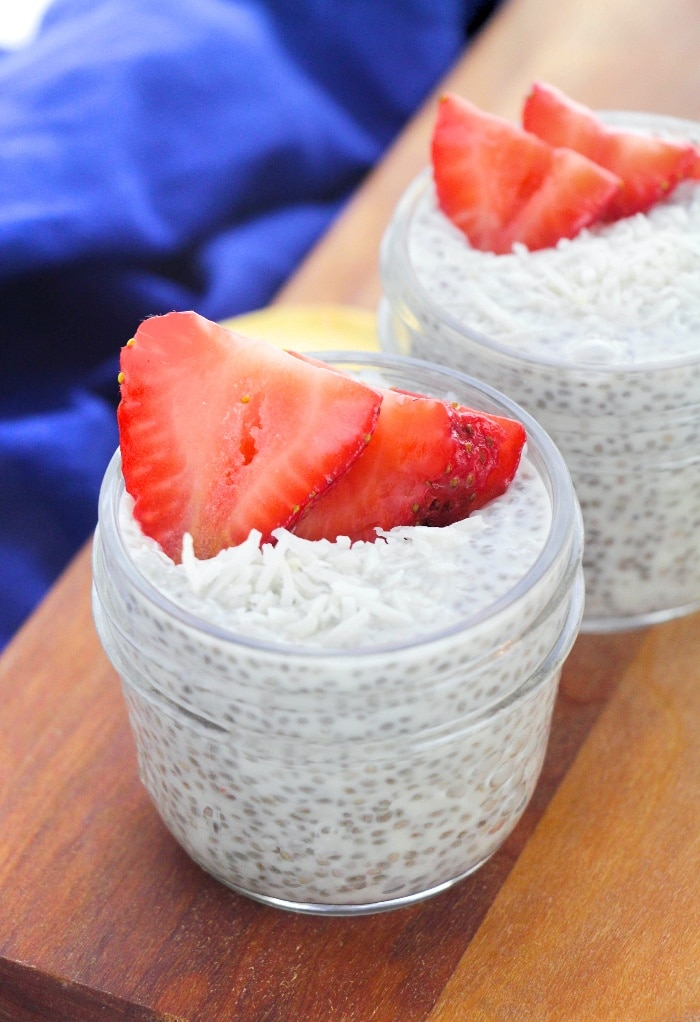 Small mason jars filled with coconut chia pudding topped with fresh strawberries.
