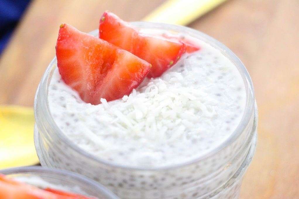 A horizontal view of the top of chia pudding in a clear jar with a fresh diced strawberry on top.