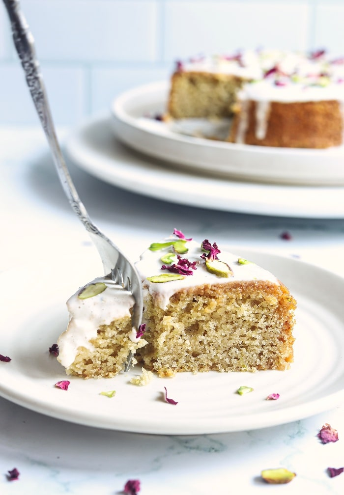 A slice of Persian love cake on a white plate with a fork digging into it ready to eat.