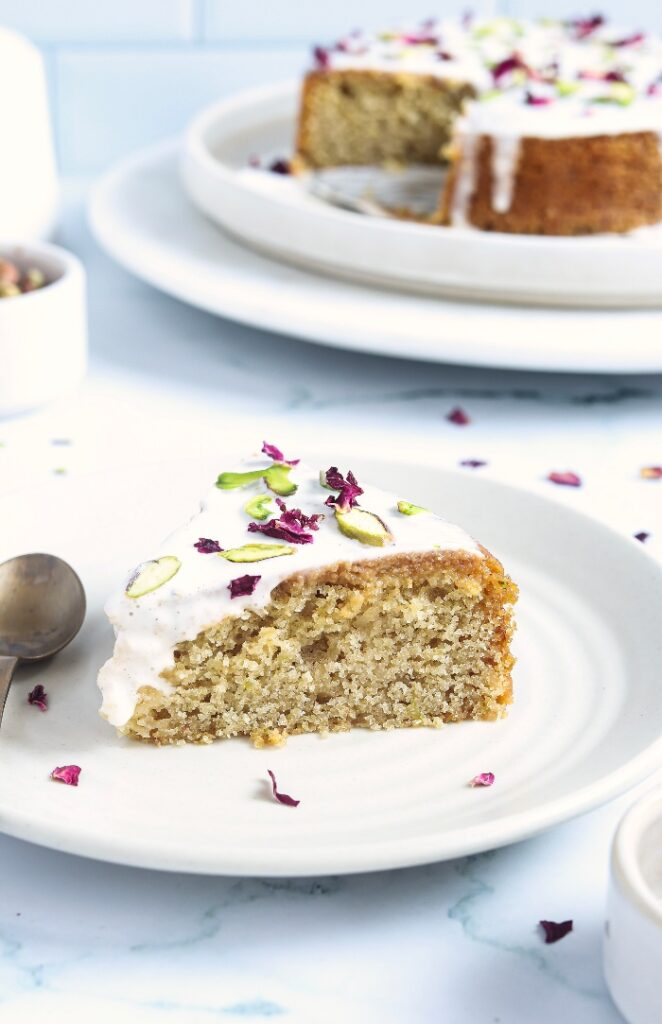 A slice of Persian cake on a white plate ready to enjoy.