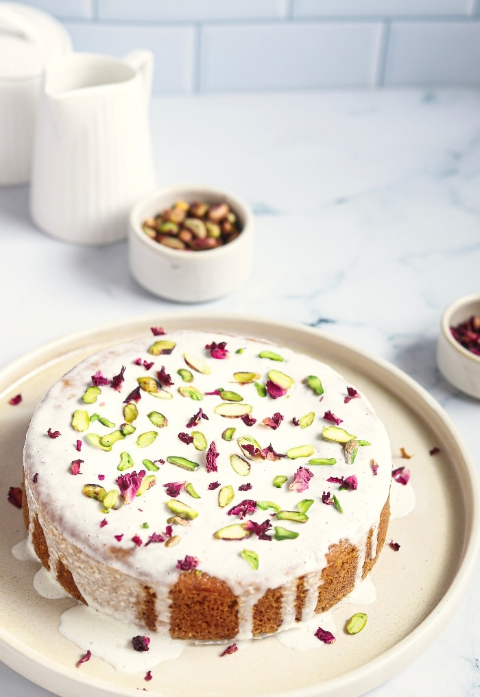 Persian love cake topped with pistachios and rose petals on a white serving plate.