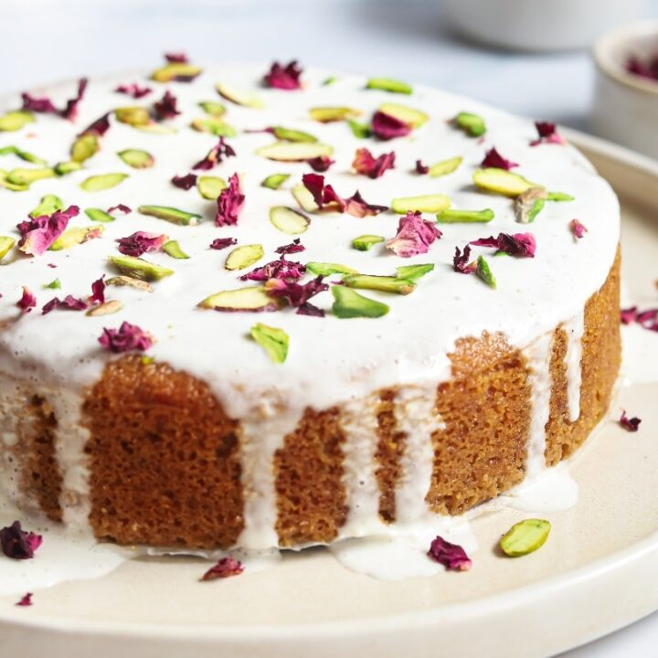 Decorated Persian love cake topped with rose petals and pistachios on a cream serving cake plate.