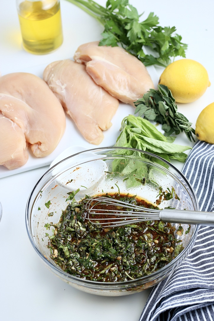 A mixture of marinade for chicken breasts in a clear mixing bowl.