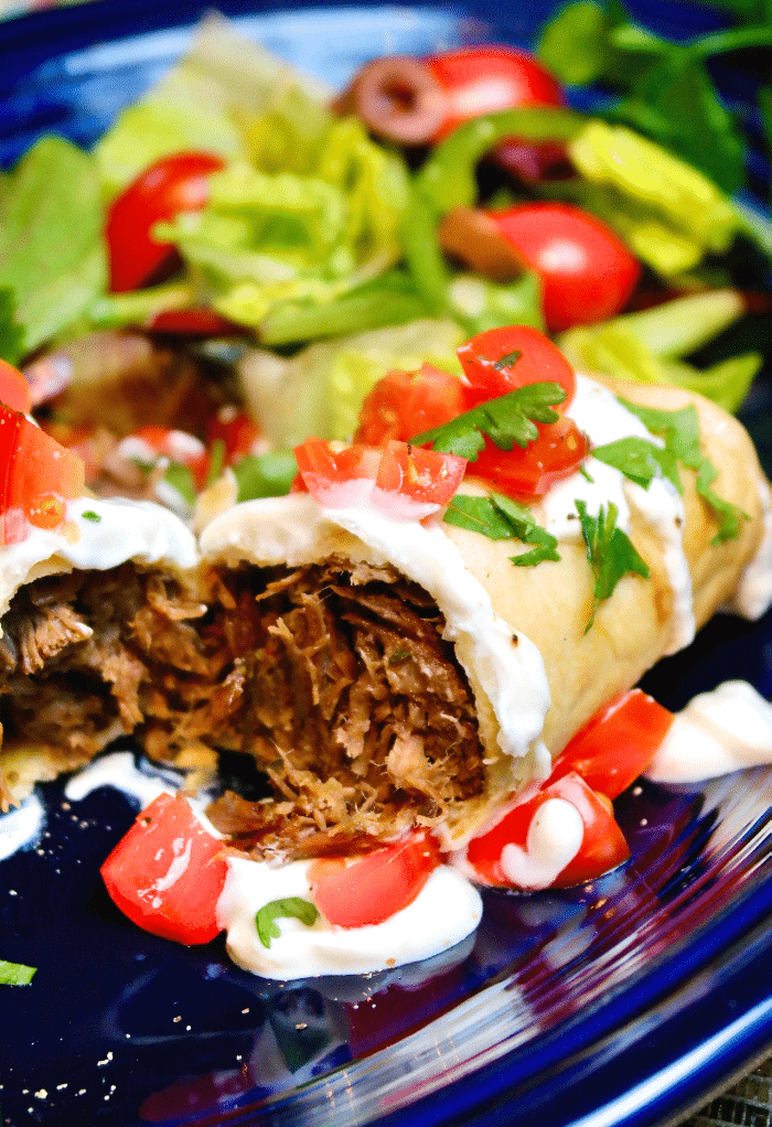 Beef chimichanga cut in half and topped with tomatoes and sour cream.