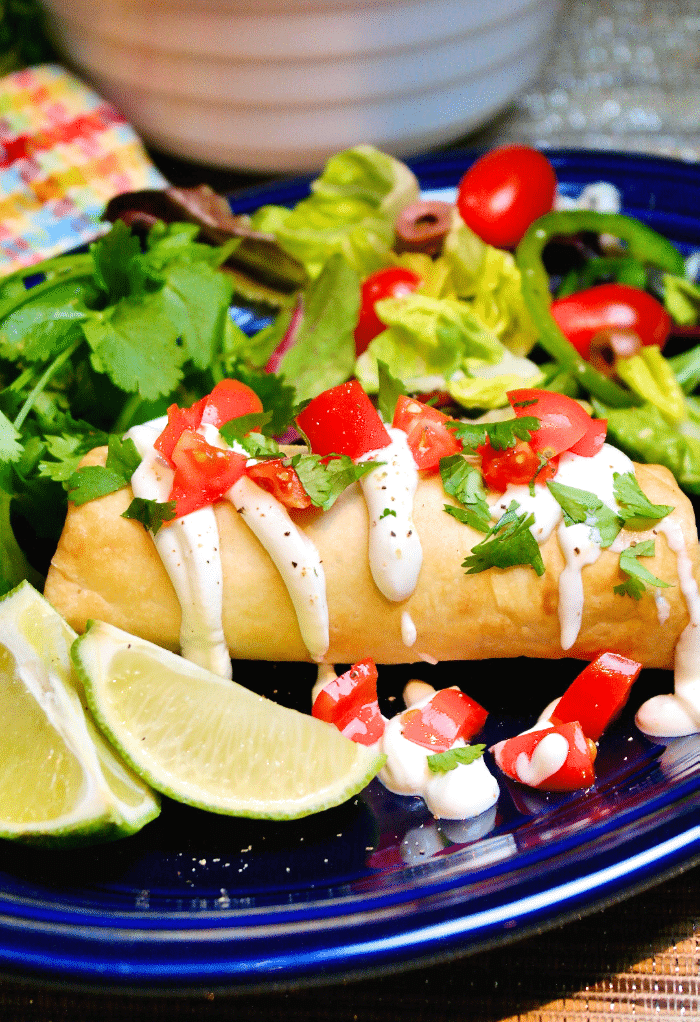 Chimichanga topped with tomatoes and sour cream on a blue plate ready to eat.