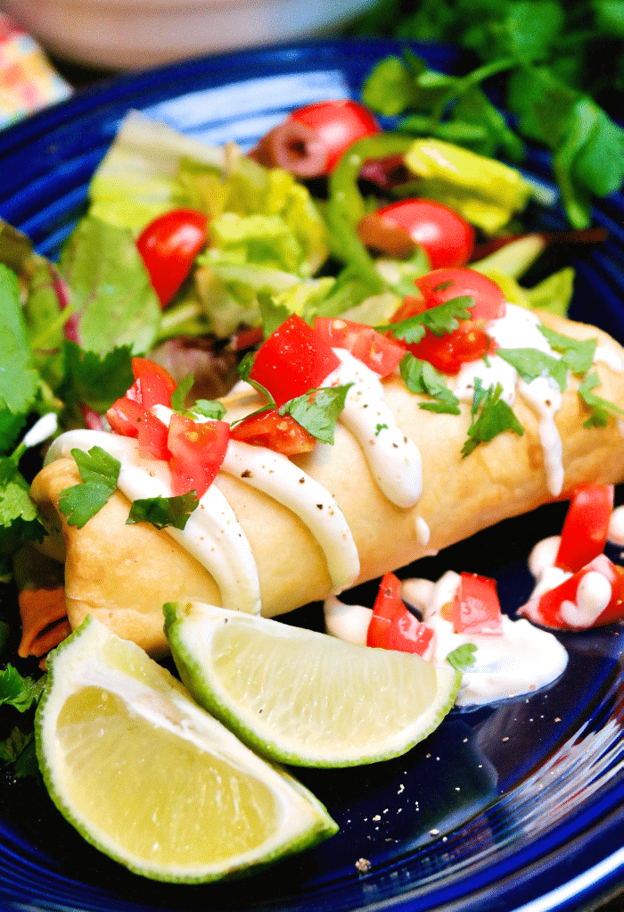 Shredded Beef Chimichanga on a blue plate topped with sour cream and tomatoes.