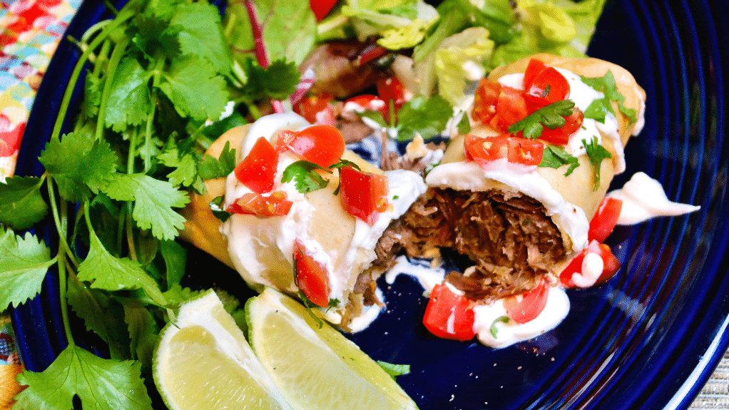 Top view of a cooked beef chimichanga topped with tomatoes and cilantro.