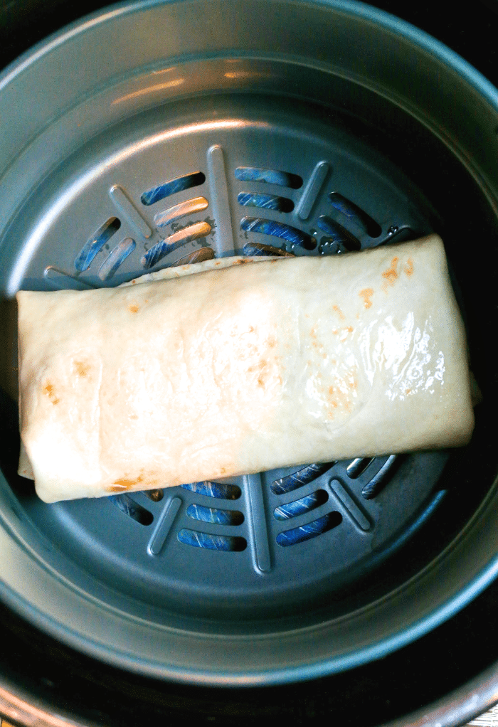 Chimichanga in an air fryer ready to be cooked.