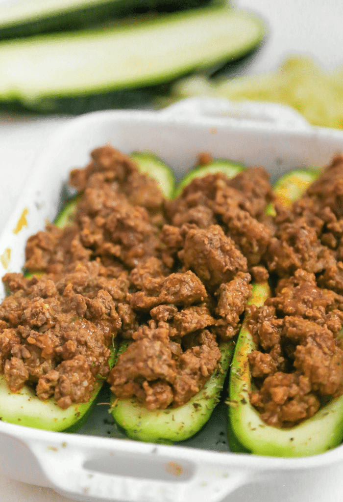 Zucchini boats stuffed with seasoned cooked hamburger meat.