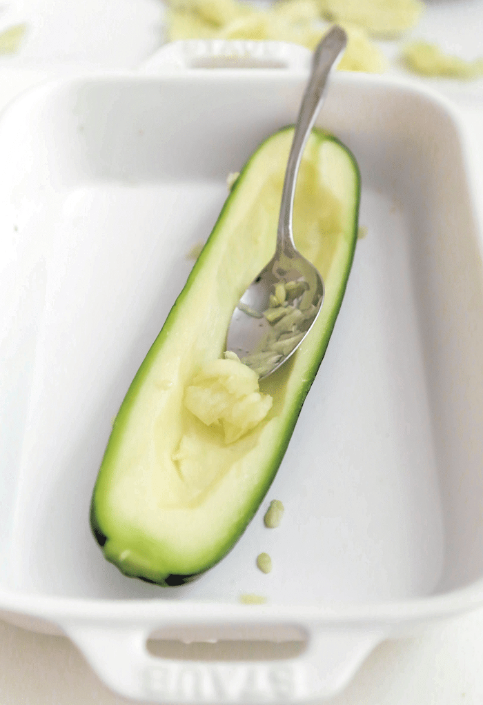 Scooping out the seeds of a zucchini getting ready to fill it with hamburger.