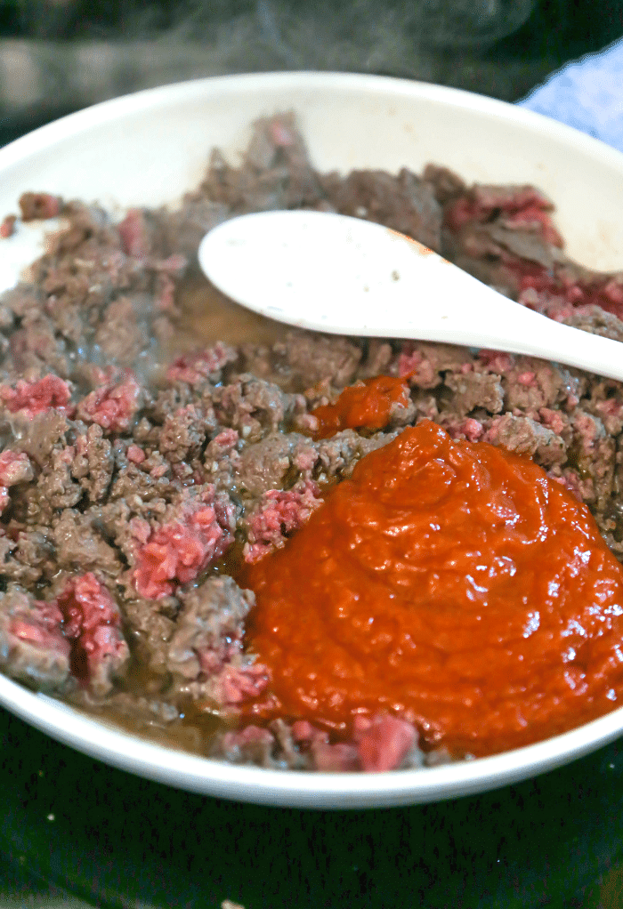 A skillet with hamburger and tomato sauce.