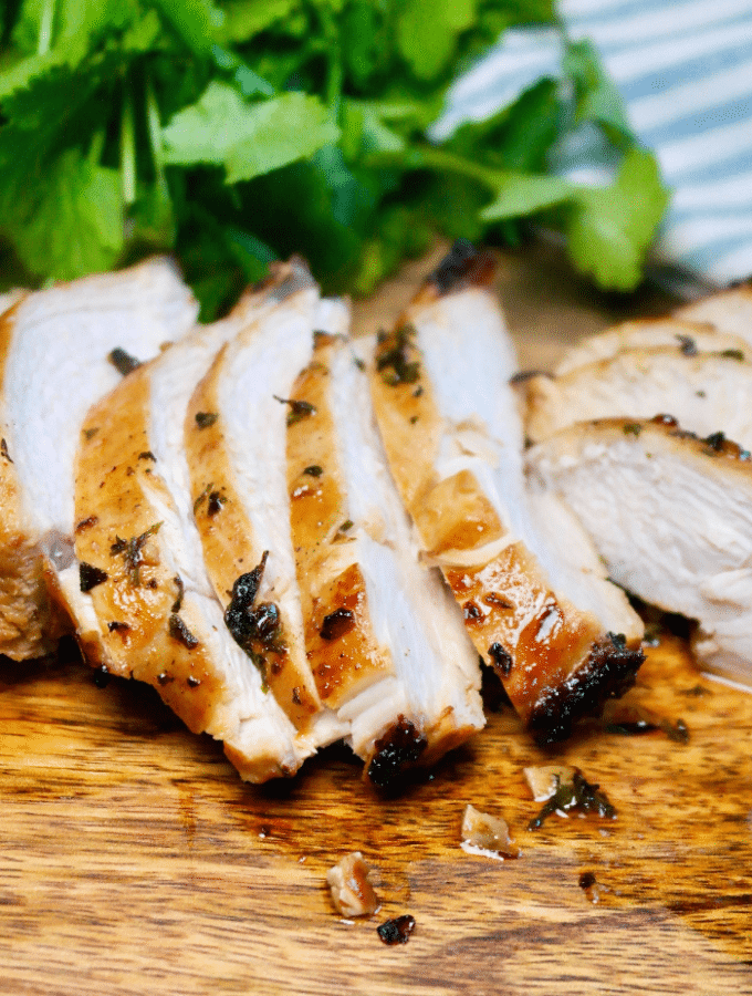 Sliced air fryer chicken breast with no breading on a cutting board.