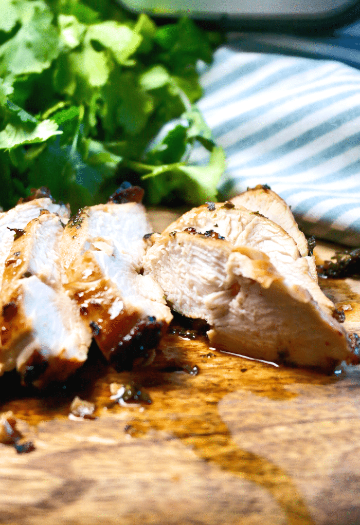 Tender chicken breast cooked in an air fryer on a wood cutting board.