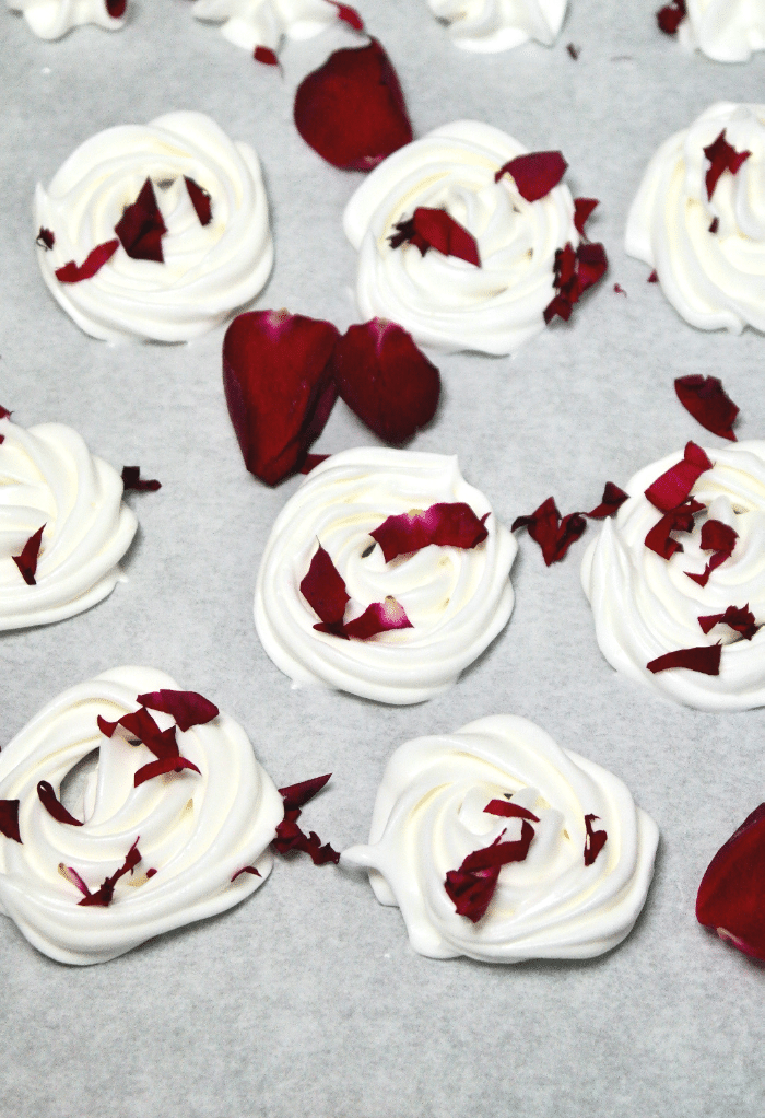 White rose meringue cookies on parchment paper before baking topped with rose petals.