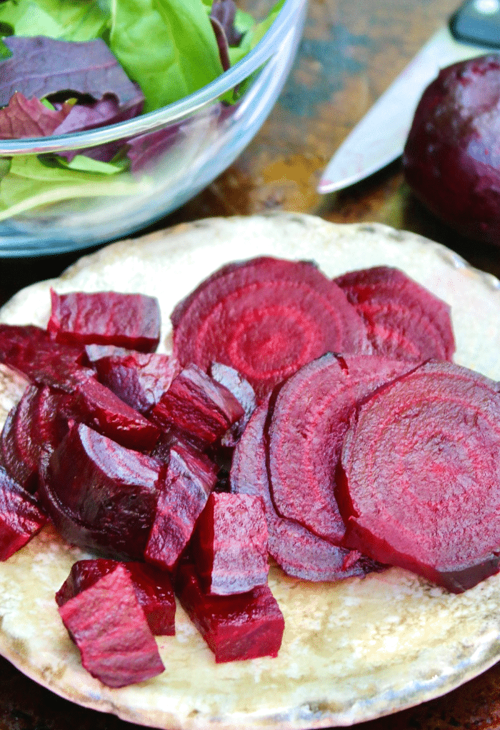 Roasted beets sliced and diced on a salad plate ready to add to a bowl of green salad.