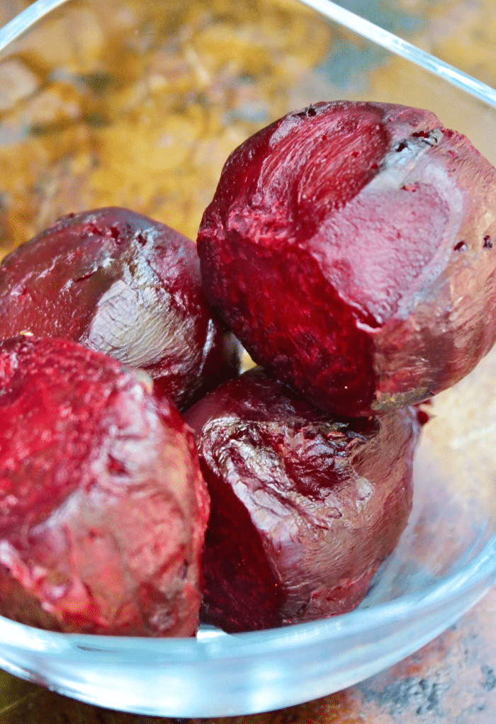 Cooked roasted beets in a clear glass bowl.