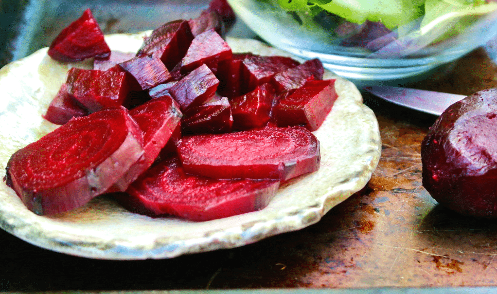 Roasted beets on on a tan plate sliced ready to eat.