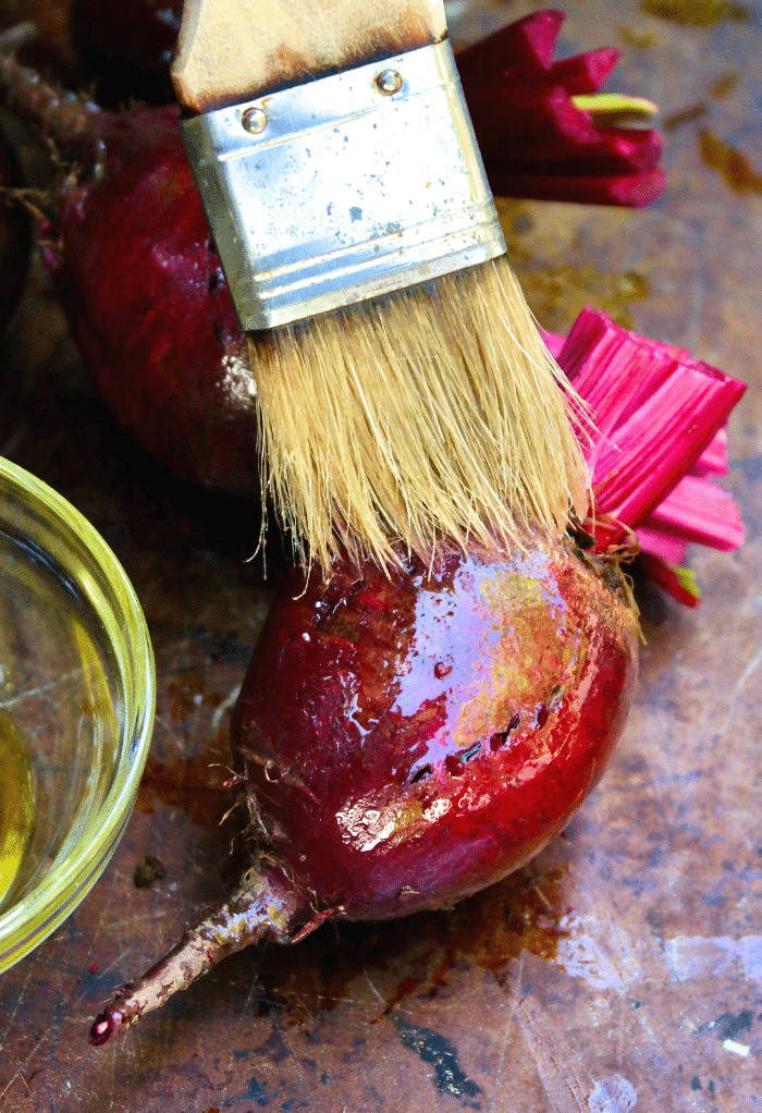 Brushing a raw beet with olive oil before roasting.