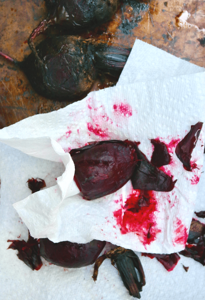 Removing skin of cooked beets with a paper towel.