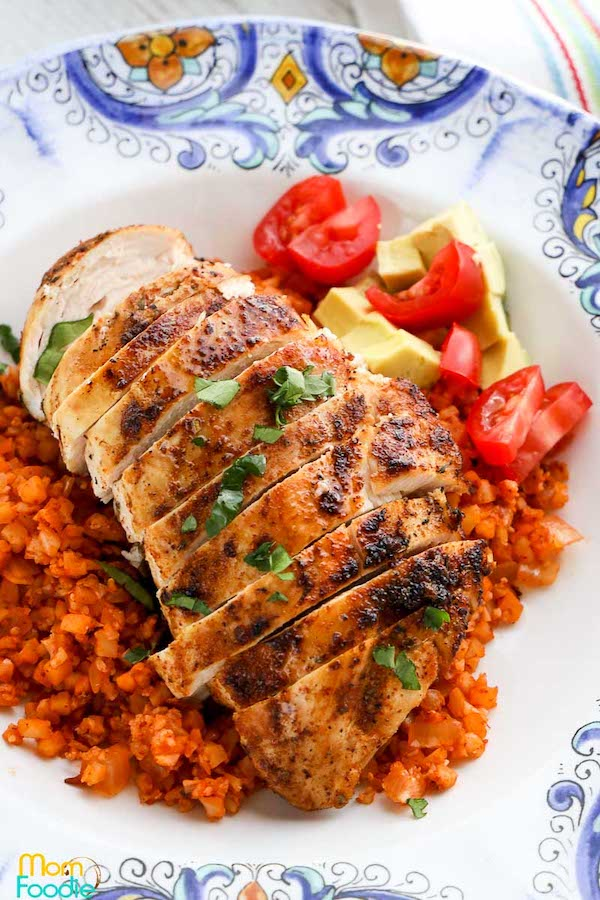 Top view of blackened chicken breasts cut into slices and surrounded by a red cauliflower rice - low carb chicken recipes