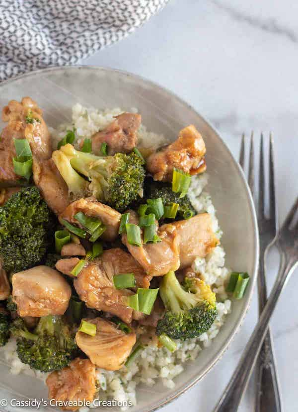Top view of cooked broccoki and chicken on a grey plate with utensils on the side