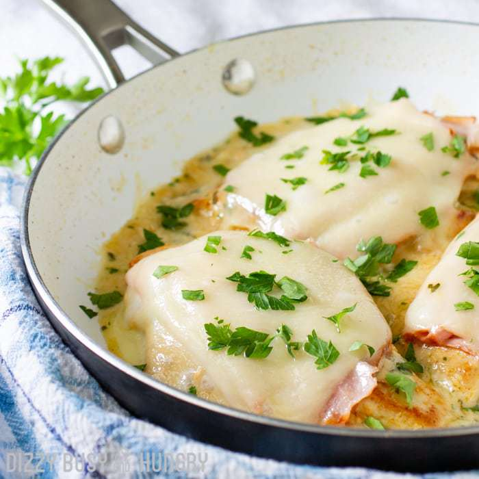 side view of cooked chicken topped with ham and melted cheese on a pan with creamy sauce