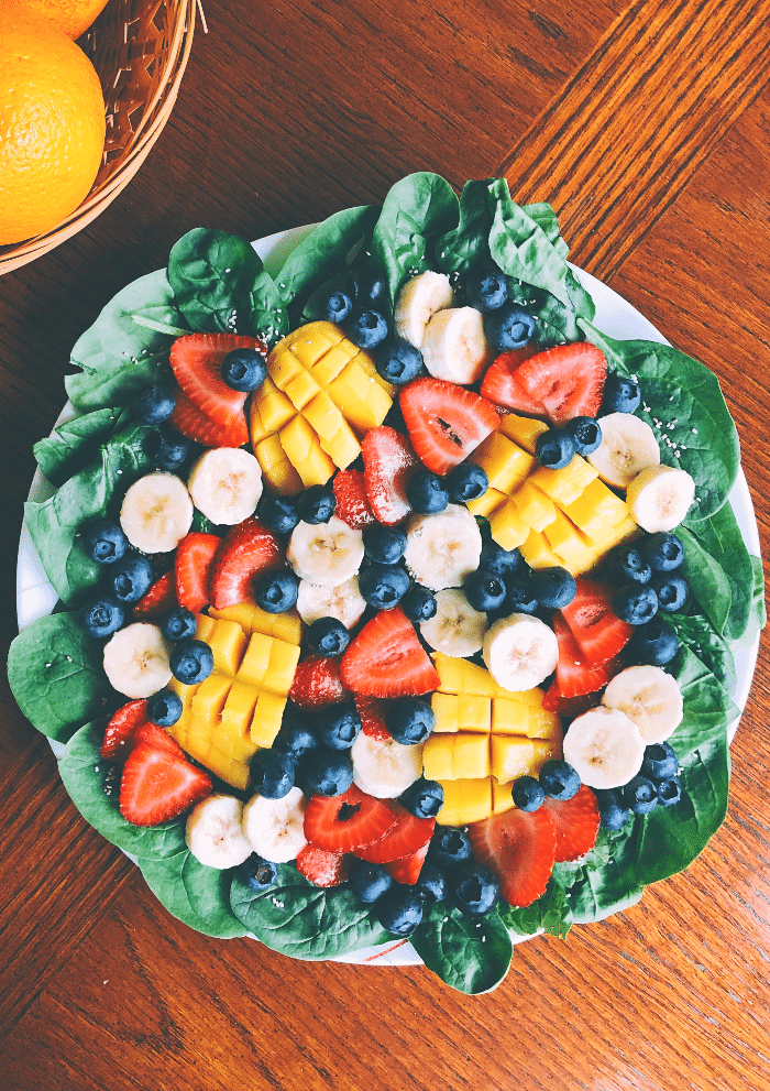 Large fruit salad over greens on a white plate.