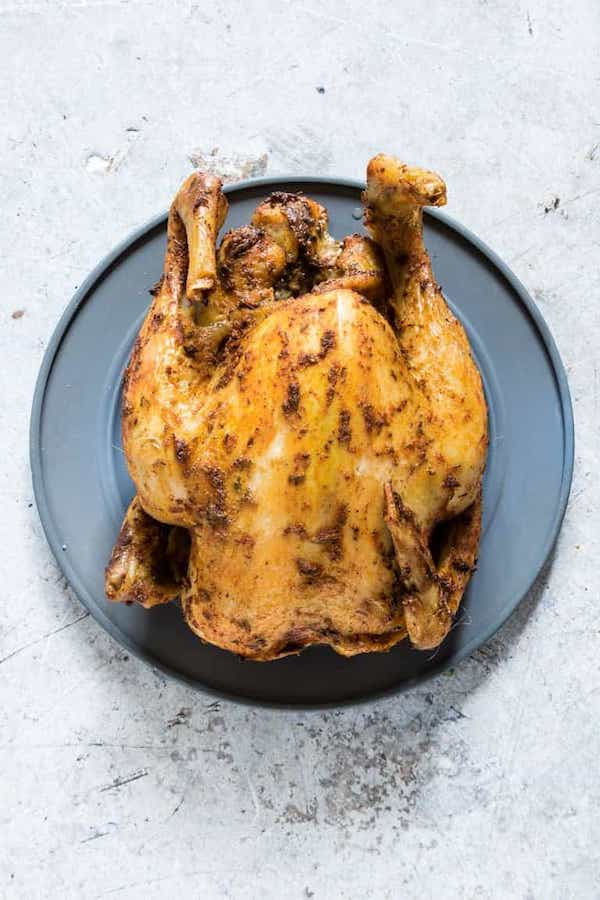 Top view of a cooked whole chicken on a blue plate - low carb chicken recipes
