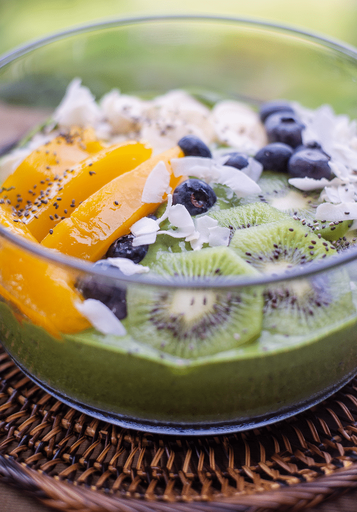 chia pudding with slices of mango and fresh blueberries in a clear bowl.