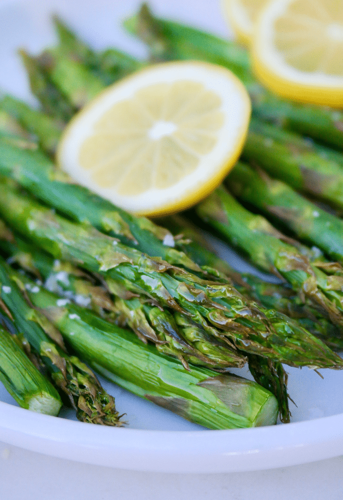 Air fryer asparagus topped with lemon on a white plate.