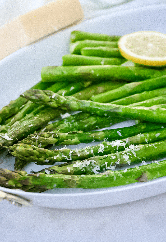 Air fryer asparagus topped with parmesan cheese on a white serving platter.