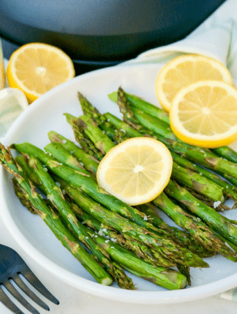 Fresh cooked air fryer asparagus topped with parmesan cheese.